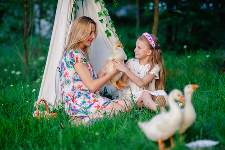 Mom and daughter sitting on the grass playing with goose