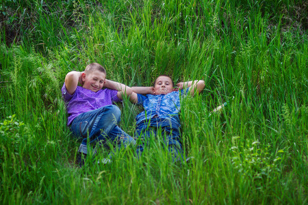 happy and joyful brothers lie on the grass in the park