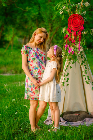 Beautiful young lady and her cute children posing in the green park at bright summer day