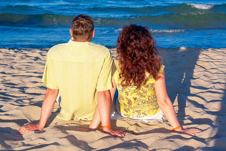 cute couple cuddles on an italian beach in gargano national park in southern italy looking at the adriatic sea