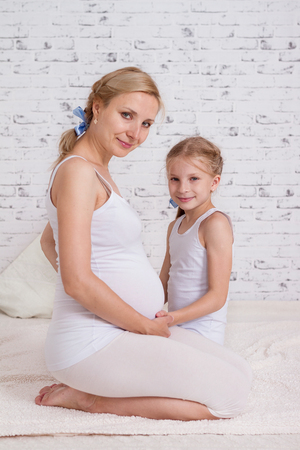 Little girl hugging her pregnant mother Stock Photo