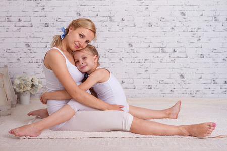 Happy daughter snuggle up to her pregnant mother Stock Photo