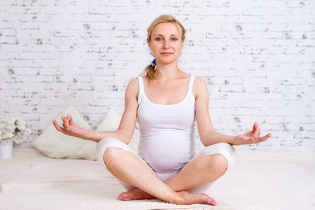 Closeup of a pregnant woman is sitting in a position lotus