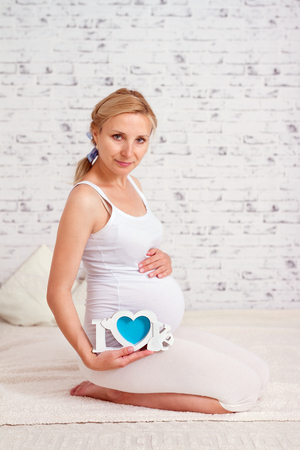 Pregnant woman hold word love on a belly on white background