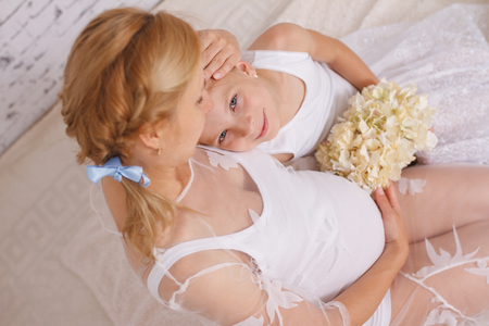 Cute smiling little girl listening belly of her pregnant mother