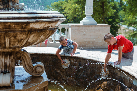 Two young boys having fun under a water fountain