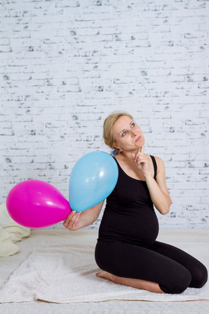 Pregnant woman with a red and blue ball