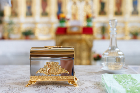 Bottle of holy water is out of focus and a box with tassels for anointing at christianity Stock Photo