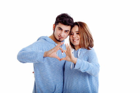 Happy and loving couple show heart with hands isolated
