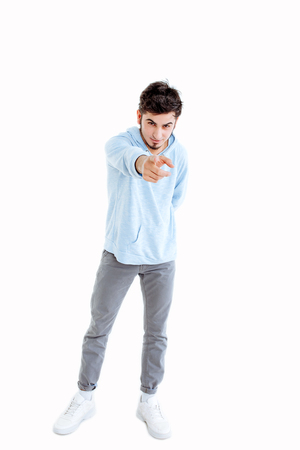 Young man wearing his finger to you Emotional, courageous face. Isolated on white. Copy space.