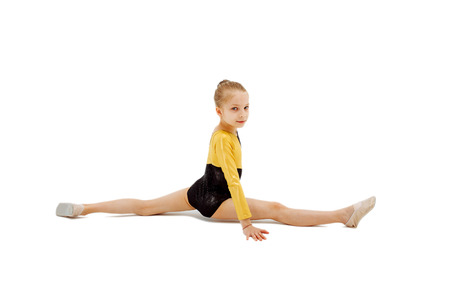 Little girl gymnast sitting in the cross splits. Isolated on white background. Sport, active lifestyle concept