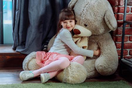 Girl gently hugs her big teddy bear 写真素材