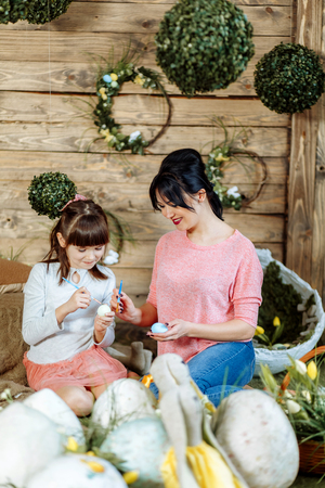 Happy easter! A mother and her daughter painting Easter eggs. Happy family preparing for Easter.
