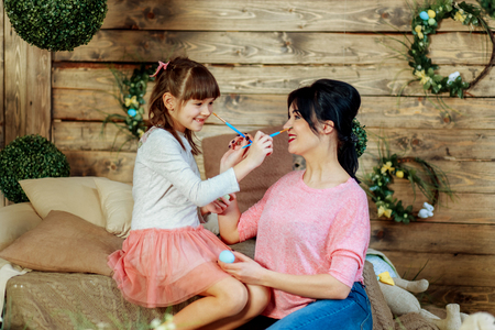 Mother showing to her child daughter how to paint Easter eggs Stock Photo