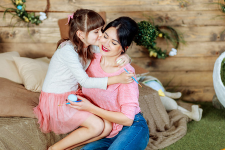 Daughter kisses her mother on the cheek, during preparation for Easter.