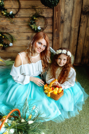 Creative mother and daughter with toy flowers preparing for Easter celebration 写真素材
