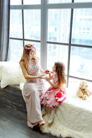 Young mother holds her little daughter standing on the windowsill