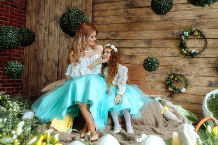 Beautiful mother and daughter in a gentle pastel spring decor