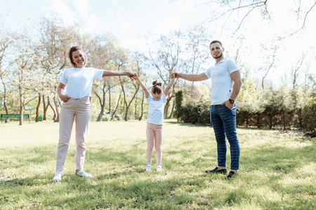 Happy family outdoors. Girl, mother, dad