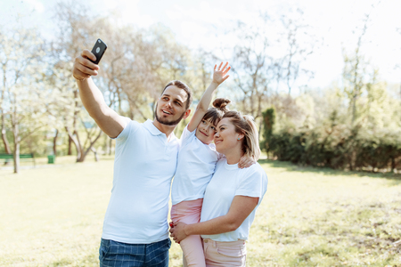 Family with child takes a selfie photo on vacation in the summer in nature 写真素材