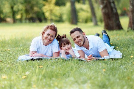Happiness and harmony in family life. Happy family concept. Young mother and father with their daughter in the park. Happy family. Carefree, happylife. 写真素材