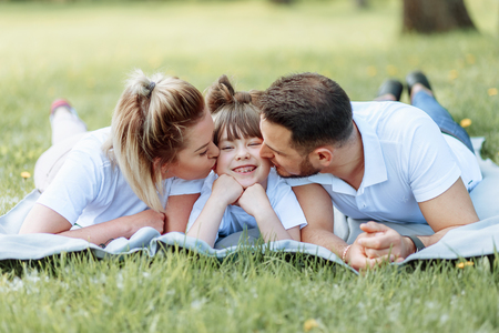 Happiness and harmony in family life. Happy family concept. Young mother and father with their daughter in the park.