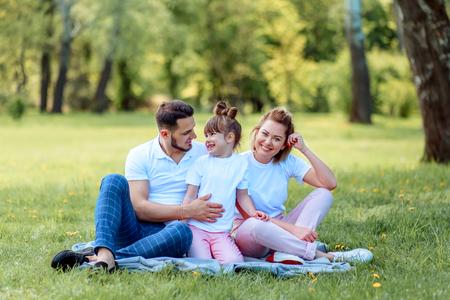 Geluk en harmonie in het gezinsleven. Gelukkig familieconcept. Jonge moeder en vader met hun dochter in het park. Gelukkig gezin. Zorgeloos, gelukkig leven.