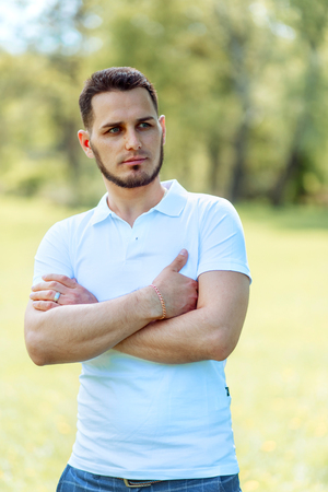 Handsome young man in white t-shirt and jeans outdoor in city park, walking toward camera, serious