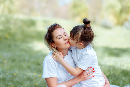 Daughter kisses mom on the cheek while playing outdoors