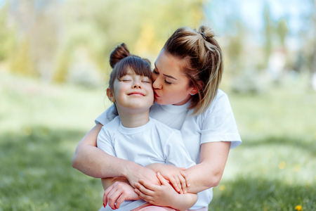 Mom kisses her daughter playing outdoors