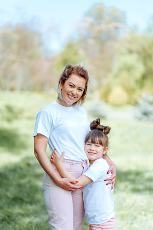 Portrait Of Mother And Daughter In Park Smiling To Camera 写真素材