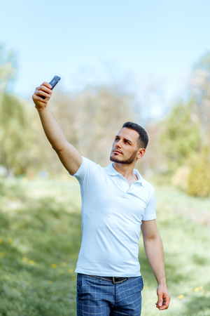Cute guy takes a selfie on the phone in the sun.