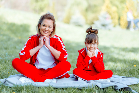 Sporty mother and daughter. women and child training in the park. outdoor sports. healthy sport lifestyle. fitness, yoga 写真素材
