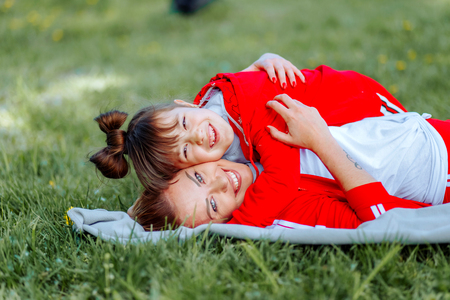Daughter lying on mothers back happily hugs her, against the background of green grass