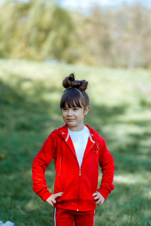 Beautiful girl in a tracksuit walking in green forest 写真素材 - 123239689