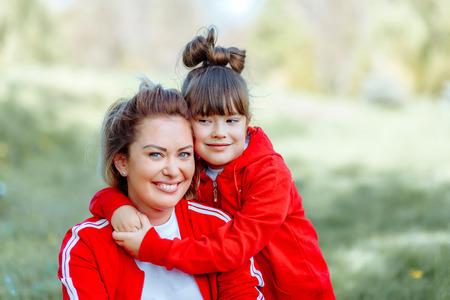 Portrait of mother and daughter playing in the park Фото со стока