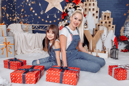 Mom and daughter with gifts on New Years Eve Фото со стока