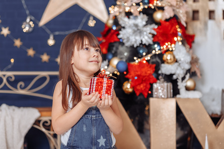 Christmas magic, girl with a gift on bokeh background Фото со стока