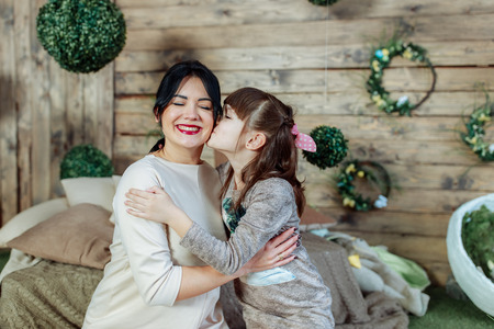 Daughter kisses mom on the cheek, mom with her daughter happily and happily lead time