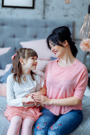 Beautiful mom and daughter are hugging, looking at camera and smiling while sitting on bed at home Фото со стока