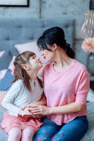 Daughter and mother sitting on the bed are drawn to each other in a kiss