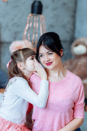 A little girl tells her mom a secret. 写真素材 - 123294746