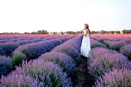 Beautiful woman in a white dress with a pink wreath walks on a lavender field