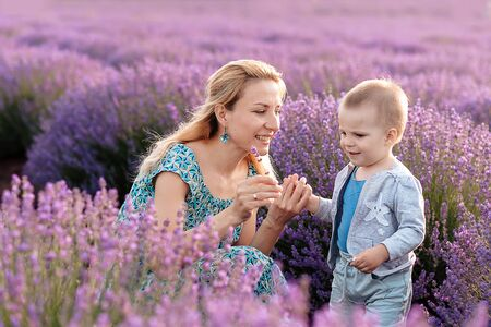 Happy young mother and her little son posing in purple field of lavender flowers