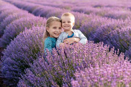 Playful little cute couple boy girl walk on purple lavender flower meadow field background, have fun, play, enjoy good. Love, bush.
