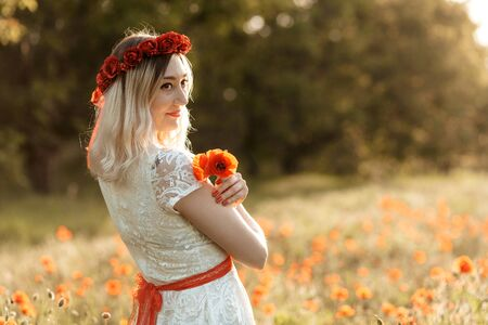Portrait of beautiful young woman with poppies in the field with a poppies bouquet 写真素材