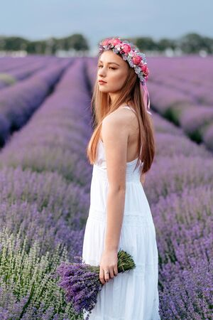 Young dreamy woman with bouquet in her hands standing in flowering lavender field, close up