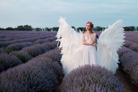 Beautiful woman in white angel outfit with wings in outdoor scenery. 写真素材