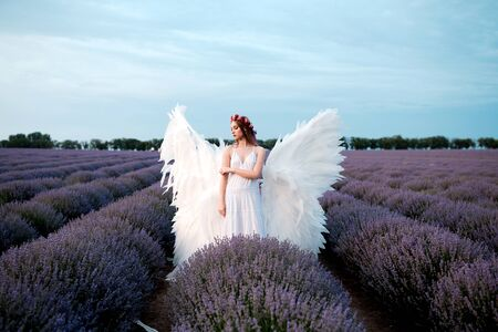 Beautiful woman in white angel outfit with wings in outdoor scenery. Archivio Fotografico