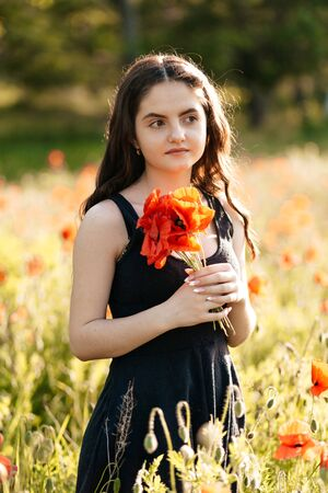 Beautiful, young woman with a bouquet of poppies in a sunset poppy field